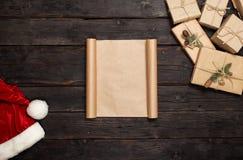 与圣诞节礼物和圣诞老人帽子的空白纸纸 免版税库存照片