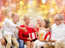 与圣诞节礼物的愉快的家庭在光 免版税库存照片
