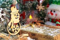 与圣诞节礼物的滑稽的雪人在一个红色灯笼和新年` s装饰的背景 库存图片