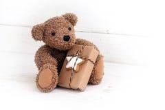 与圣诞节礼物的玩具熊坐白色绘了w 库存图片