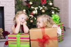 与圣诞节礼物的滑稽的孩子 免版税库存照片