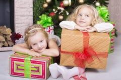 与圣诞节礼物的滑稽的孩子 免版税库存图片