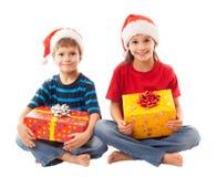 与圣诞节礼物盒的两个微笑的孩子 免版税库存图片
