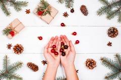 与圣诞节礼物,冷杉的圣诞节背景分支,杉木锥体,红色装饰 女性现有量 平的位置,顶视图 免版税库存照片