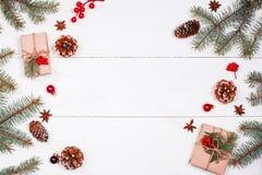 与圣诞节礼物,冷杉的圣诞节背景分支,杉木锥体,雪花,红色装饰 Xmas和新年好 免版税库存图片