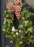 与圣诞节花圈和弓的前门 图库摄影