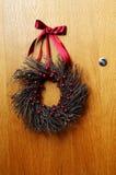 与圣诞节花圈的木门 免版税图库摄影
