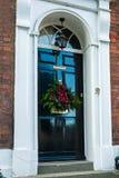 与圣诞节花圈的门 库存图片