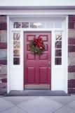 与圣诞节花圈的门 免版税库存照片