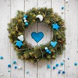 与圣诞节花圈装饰蓝色的白色木背景 免版税库存图片