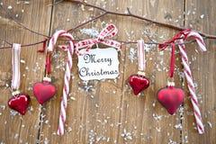 与圣诞节装饰品和糖果的木分行 免版税库存照片
