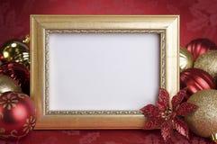 与圣诞节装饰品的空的金框架在红色背景 免版税库存图片