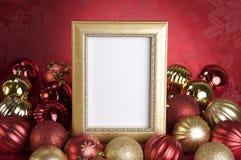 与圣诞节装饰品的空的金框架在红色背景 免版税库存照片
