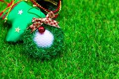 与圣诞节装饰品的高尔夫球在绿草 库存图片