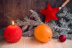 与圣诞节装饰的两个红色蜡烛在木背景 库存照片