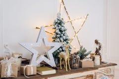 与圣诞节装饰的冬天静物画戏弄鹿、星和礼物盒在轻的背景 软的焦点,被弄脏 库存图片