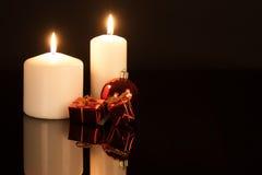 与圣诞节装饰的白色蜡烛反对黑背景 库存图片