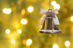 与圣诞节铃声和金黄光的圣诞卡 库存图片