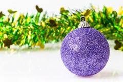 与圣诞节闪亮金属片的唯一紫色装饰品 免版税库存图片