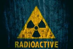 与在一个巨型的混凝土墙上绘的词放射性下面的放射性致电离辐射危险标志 免版税库存照片