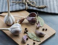 与在一个木板和布料和新的香料的自创大蒜安置的月桂叶 库存照片