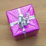 与在一张发光的紫色纸包裹的丝带的圣诞节礼物 免版税图库摄影