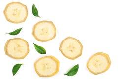 与在与拷贝空间的白色背景隔绝的叶子的香蕉切片您的文本的 平的位置,顶视图 库存图片