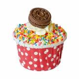与在与裁减路线的白色背景和曲奇饼的彩虹杯形蛋糕隔绝的香草奶油 免版税库存照片
