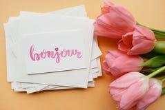 与在书法样式写的词bonjour的卡片 最小的花卉构成 免版税库存照片