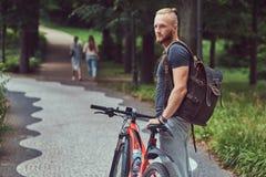 与在便衣和胡子的一个英俊的红头发人男性穿戴的一个时髦的理发在有自行车的公园走和 免版税库存图片