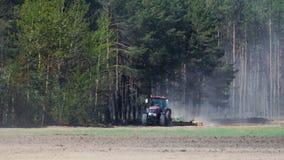 与在具球果森林背景拴住的圆盘耙的拖拉机红色把柄多灰尘的棕色土壤  股票录像