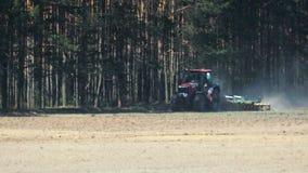 与在具球果森林背景拴住的圆盘耙的拖拉机红色把柄多灰尘的棕色土壤  股票视频
