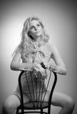 与在典雅的裸体女衬衫的有吸引力的公平的头发模型诱惑坐椅子,演播室射击 方式纵向 图库摄影