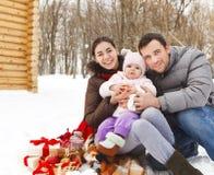 与在冬天野餐的愉快的微笑的家庭 免版税库存图片