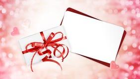 与在圣诞节明亮的ligh隔绝的红色丝带弓的礼品券 图库摄影