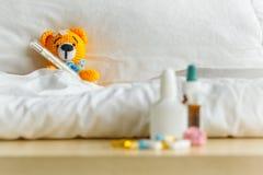 与在头的温度计的黄色玩具熊和在桌上的膏药在白色卧室和药剂 图库摄影