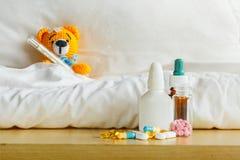 与在头的温度计的黄色玩具熊和在桌上的膏药在白色卧室和药剂 免版税库存图片
