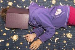与在她的面孔的一本书睡觉的女孩 免版税库存图片