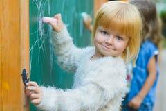 画与在室外的黑板的白垩的逗人喜爱的孩子 库存图片