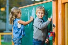 画与在室外的黑板的白垩的逗人喜爱的孩子 免版税图库摄影