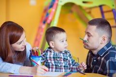 与在家一起使用小孩的男孩的年轻愉快的家庭 免版税库存照片