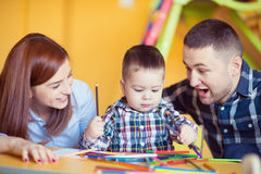 与在家一起使用小孩的男孩的年轻愉快的家庭 免版税库存图片
