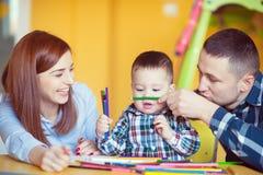 与在家一起使用小孩的男孩的年轻愉快的家庭 库存照片