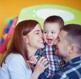 与在家一起使用小孩的男孩的年轻愉快的家庭 库存图片