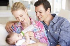 与在家哺养在沙发的婴孩的年轻家庭 免版税库存照片