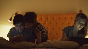 与在家在床上的小儿子的愉快的家庭使用片剂计算机和智能手机观看的电影和动画片的  股票视频