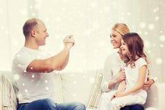 与在家拍照片的照相机的愉快的家庭 免版税库存照片