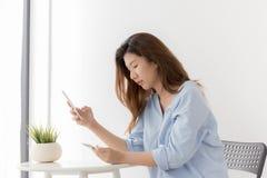与在家智能手机的亚洲妇女购物,新一代wome 免版税库存照片