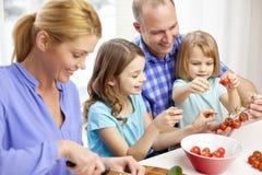 与在家烹调两个的孩子的愉快的家庭 图库摄影