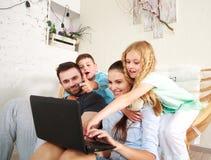 与在家看在膝上型计算机的两个孩子的愉快的家庭乐趣 库存照片